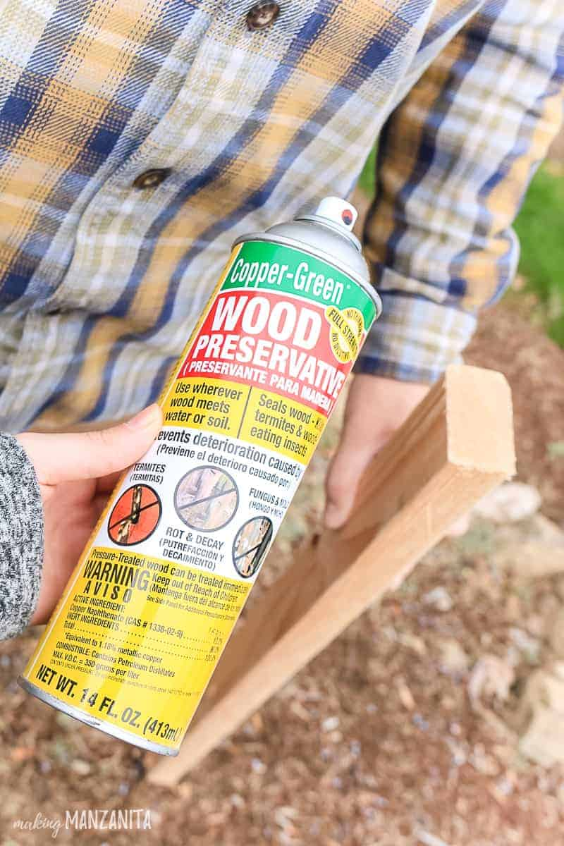 Bottle of spray copper green wood preservative held in front of a piece of 2x4