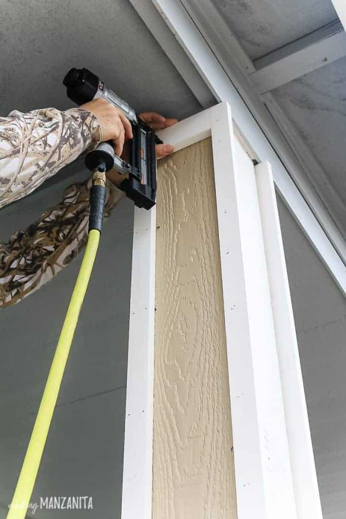 shows an arm using a brad nailer on the outside trim of a gray house