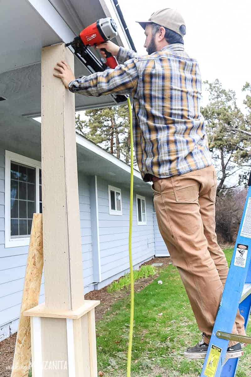 Man standing on ladder adding column wrap to porch post make with exterior siding and trim for a craftsman style
