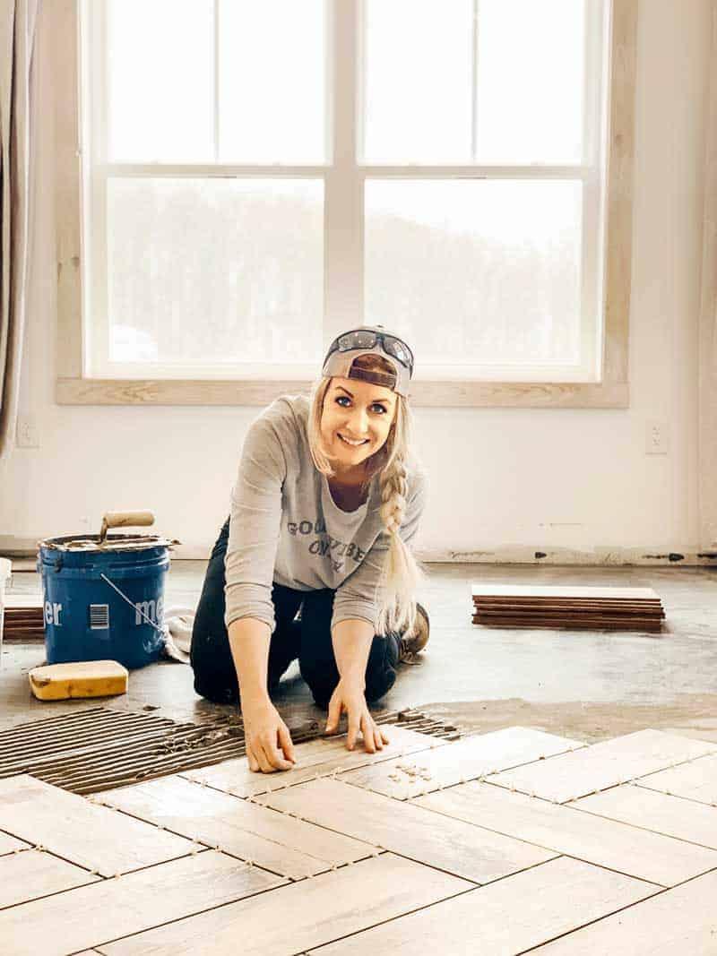Woman tiling floor in a herringbone pattern wearing a backwards hat