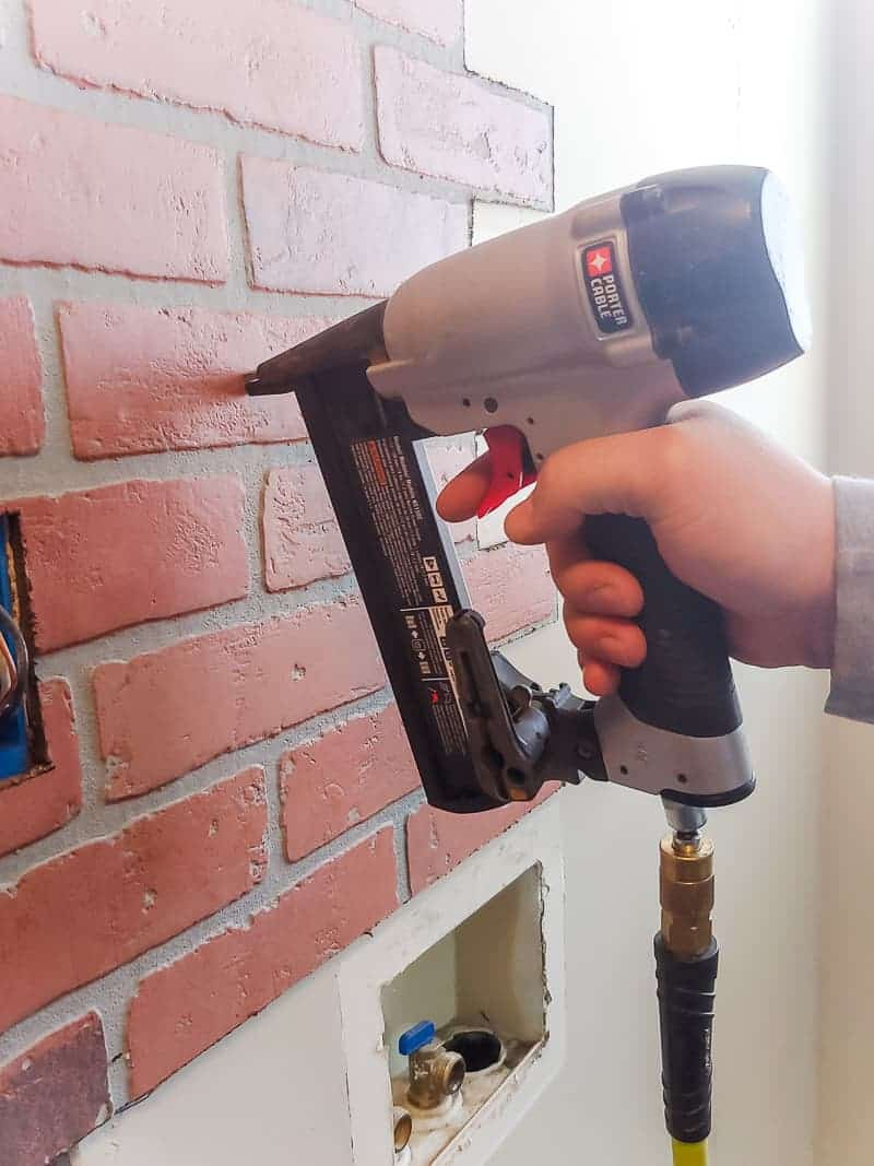 Man attaching fake brick paneling to the wall with a staple gun