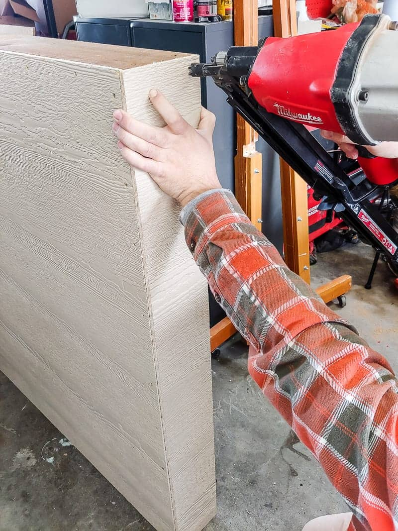 Attaching the top sheet to the siding sheet using a framing nailer.