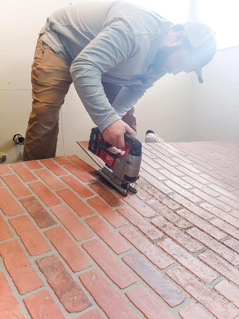 Man using jig saw to cut faux brick panels before installing on the wall