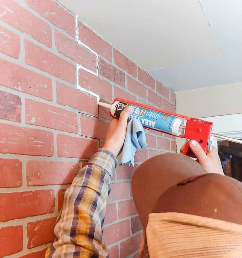 Man caulking the joint between two faux brick wall panels with DAP Alex Flex caulk
