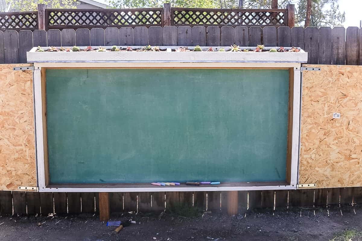 Front view of the large chalkboard on the fence with rectangular succulent plant box on top.