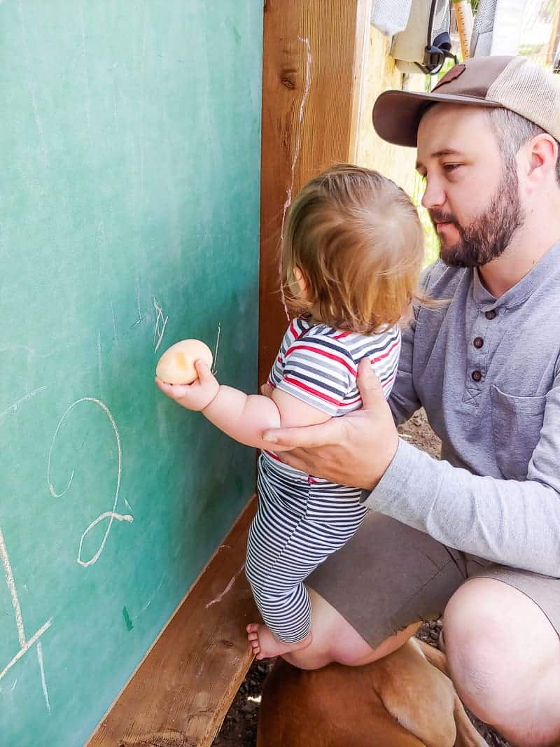 Dad holding a baby in front of the kids chalkboard while the baby is drawing.