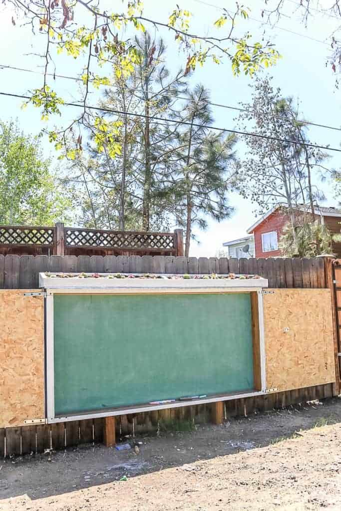 shows a giant chalkboard on the back fence with doors opened and life roof with succulents on top