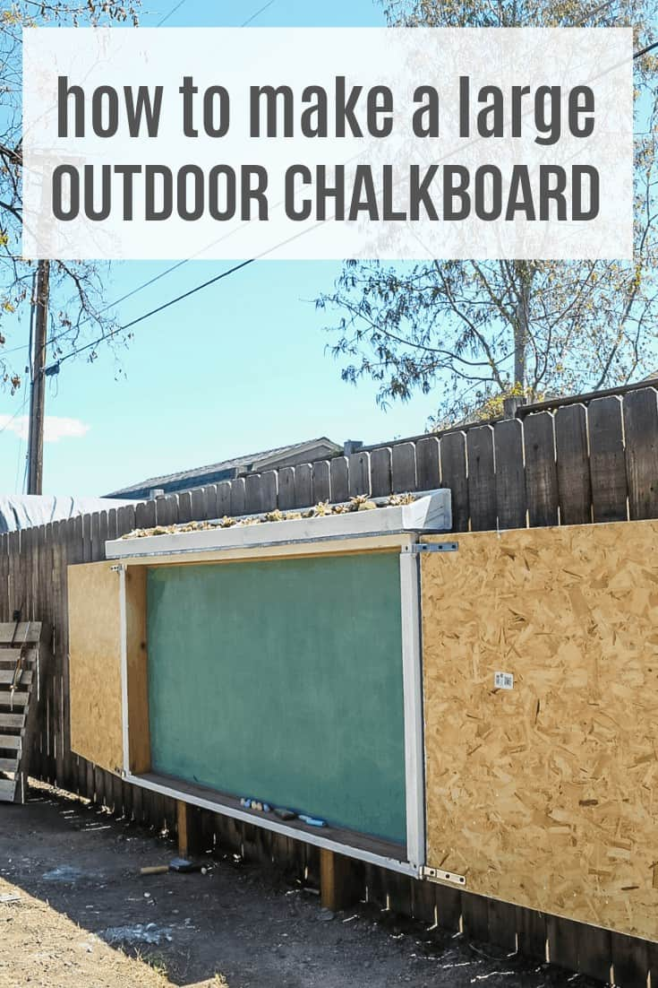 Large outdoor chalkboard in front of fence in backyard with doors for protection from weather with text overlay that says how to make a large outdoor chalkboard