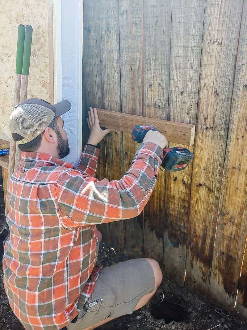 Man attaching a wood support on the fence for the large chalkboard.