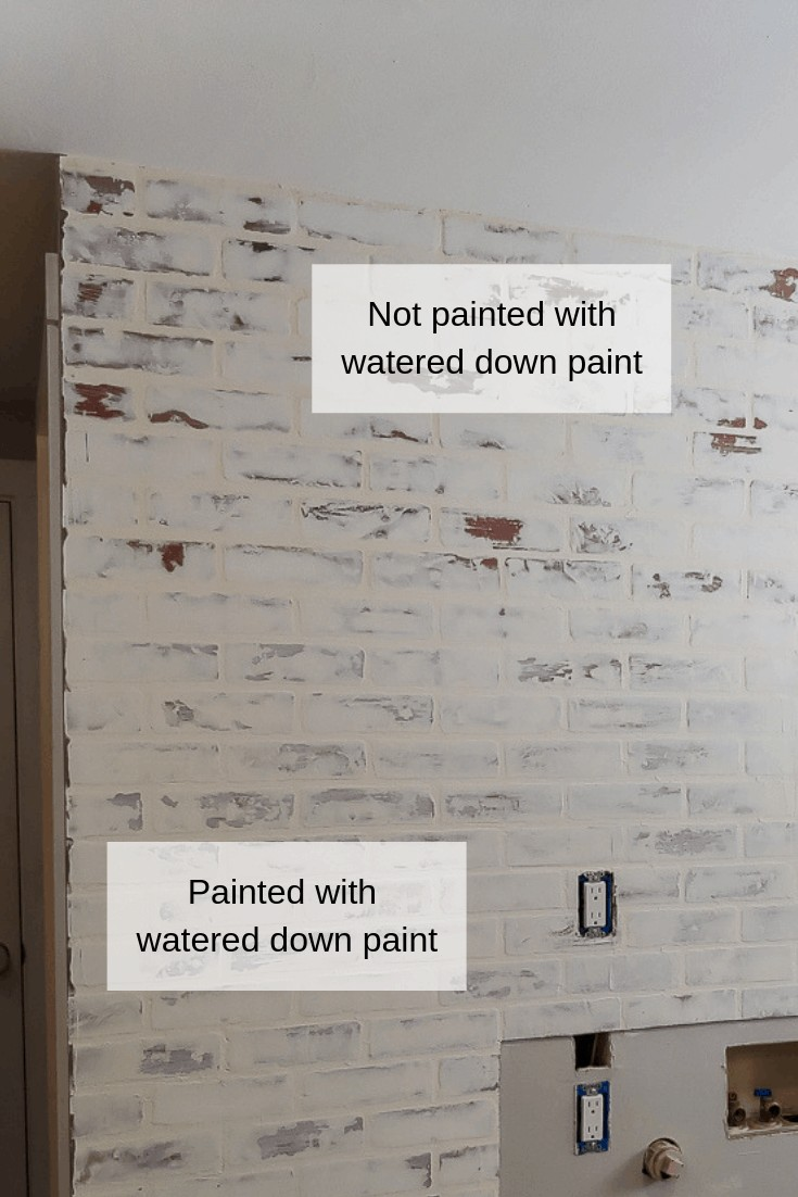 Fake brick wall with german schmear treatment using joint compound that turned orange-ish. Image shows the bottom part of the wall painted with watered down paint to lighten it up and seal the wall. The top portion shows the wall unpainted and unsealed.