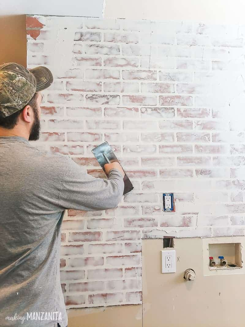 Man applying joint compound with a trowel over fake brick wall paneling to create a german smear finish