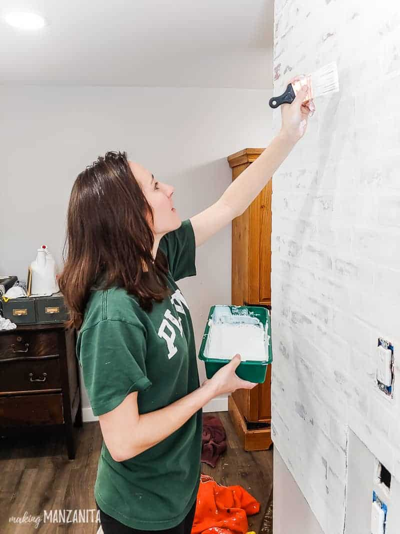 Woman painting fake brick wall panels with watered down white paint to seal german schmear treatment