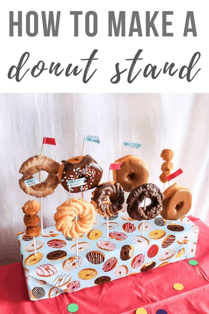 DIY donut stand with donuts standing on sticks with tiny statement flags on top of the table with text overlay that says How to Make a Donut Stand.