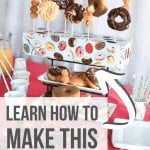 Donut stand in the center of the party food like orange juice, cups and stirrers, mixed berries and spoons on top of the table with text overlay that says Learn How to Make this Donut Stand.