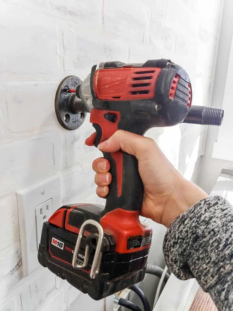Adding pipe bracket to wall using drill