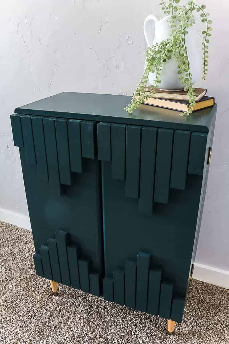 Finished dark green boho style cabinet with aztec pattern on front displayed with farmhouse home decor.