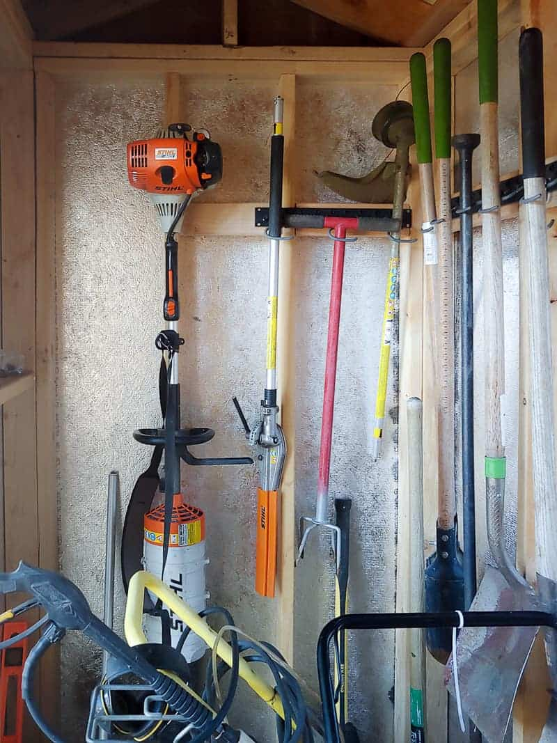 Closer look of the garden tools in wall mounted storage system.