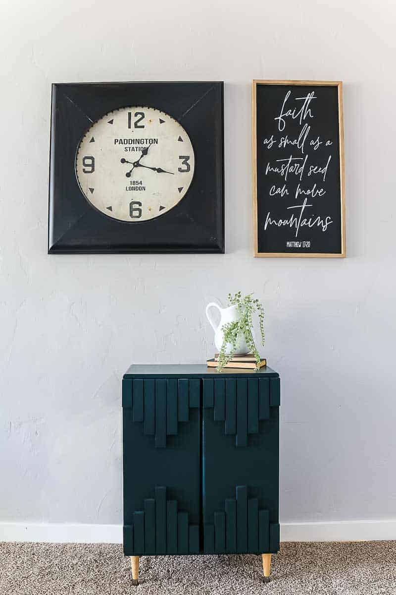 Full image of dark green aztec style cabinet with tribal pattern with clock and frame above and farmhouse decor on top of it.