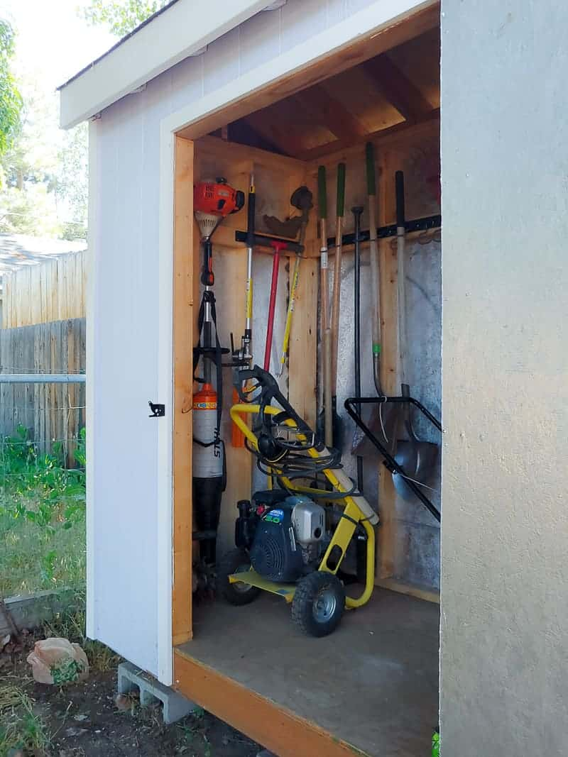 Side view of garden tool storage's opened door showing the organized garden tools in a wall mounted system and other garden machines