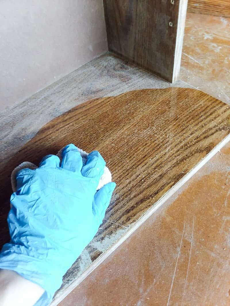 Hands wearing gloves wiping the sanded cabinet with wet cloth and TSP