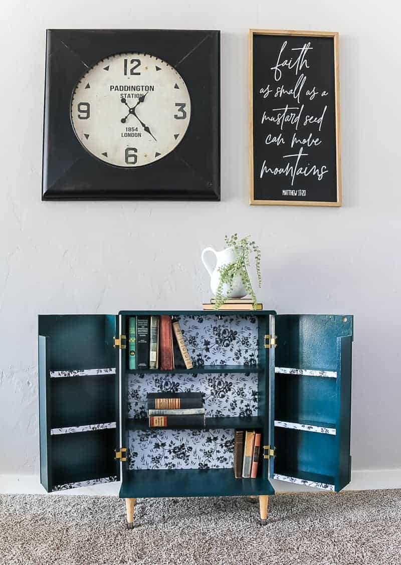 Full image of the opened dark green boho style cabinet showing the inside with books, clock and frame above it and farmhouse decor on top.