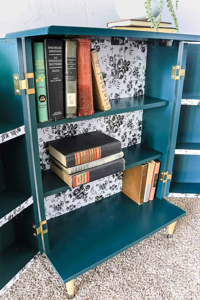 Opened dark green boho style cabinet showing the inside with vintage books on the shelves.