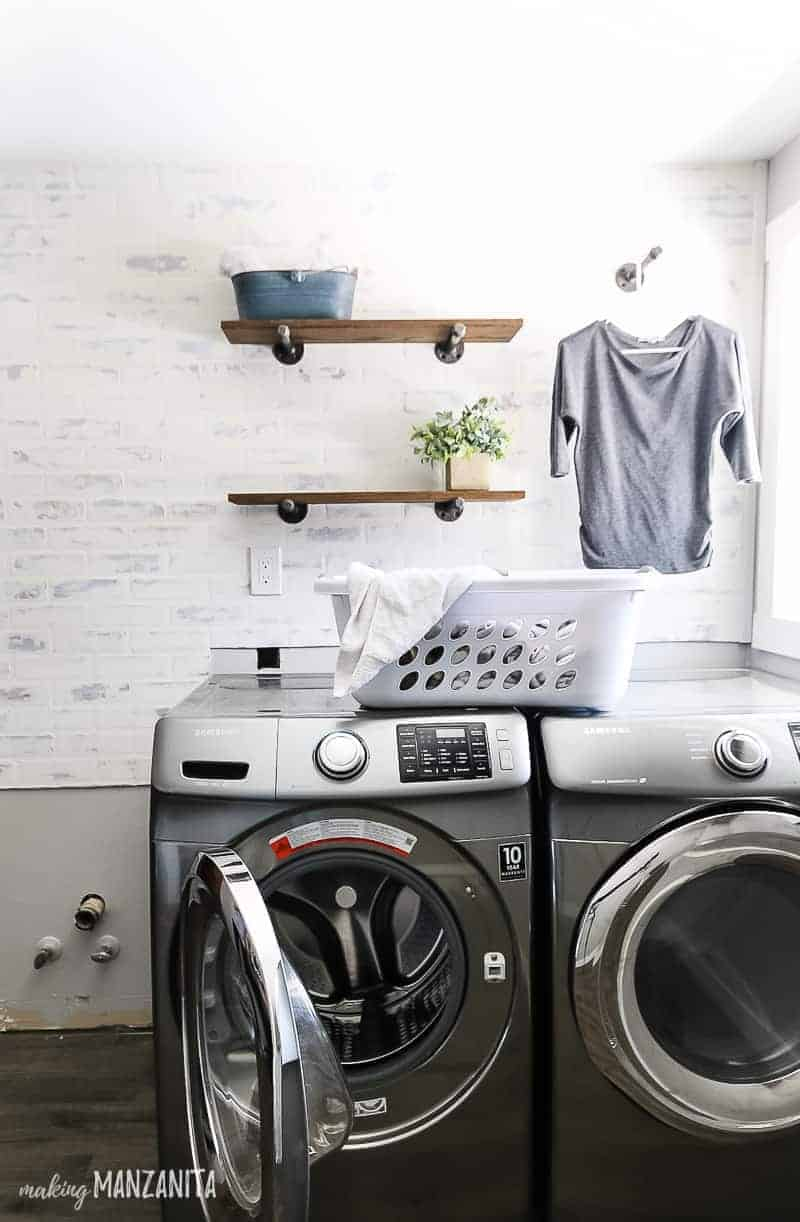 Full image of laundry room shelving, with clothing hanging on the side and washing machines below.
