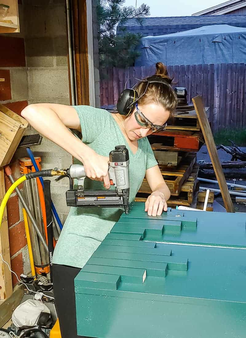 Woman in headphones wearing safety glasses attaching the trim pieces onto the cabinet.