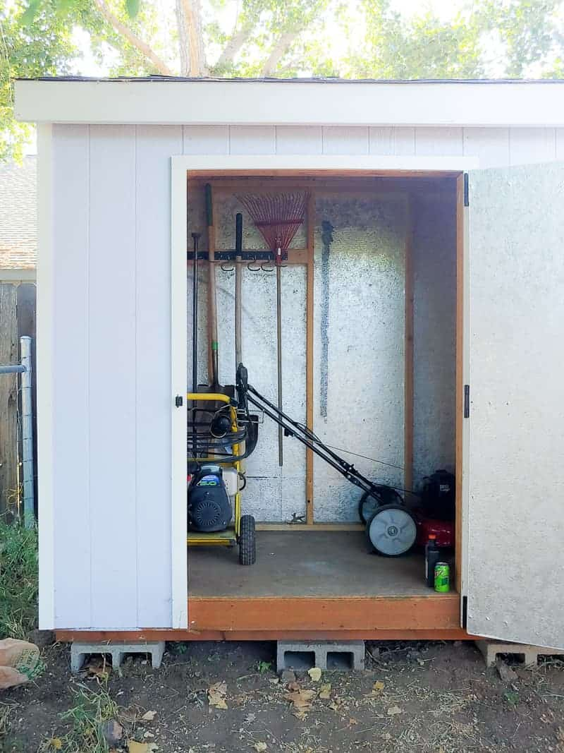 Opened door of garden tool storage showing garden hanged on wall, lawn mower and other gardening machines.