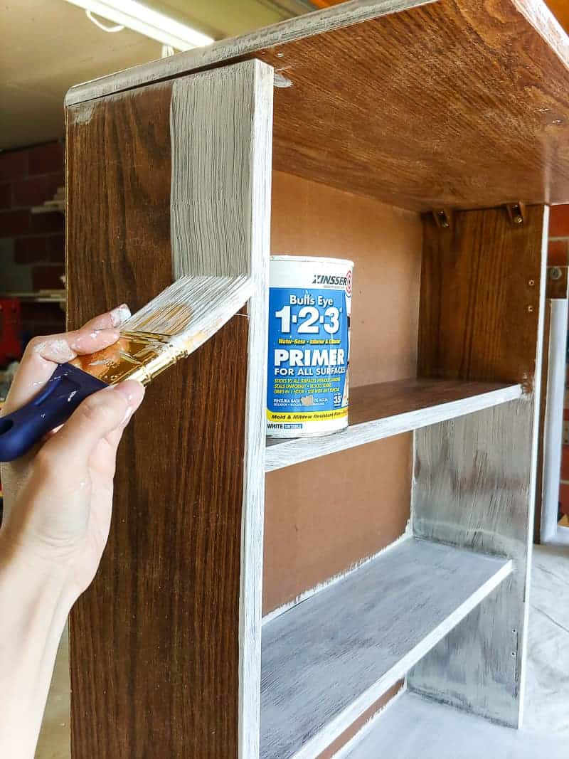 Painting cleaned cabinet with primer using paint brush.