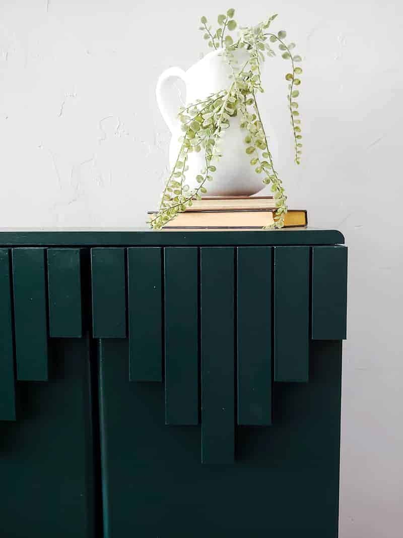 Dark green boho style cabinet focusing the right side trim pieces design with farmhouse decor on top of it.