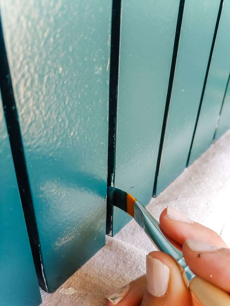 Painting the gaps of the trim pieces with small artist paint brush