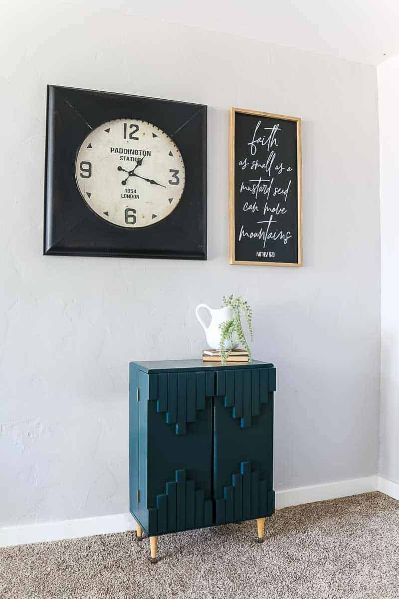 Slight side view of dark green boho style cabinet with industrial large clock and framed quote sign above it with white pitcher and vintage books on top
