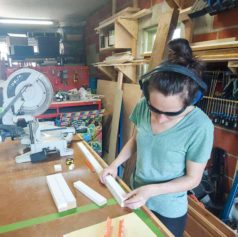 woman in headphones and safety glasses measuring trim pieces for cutting.