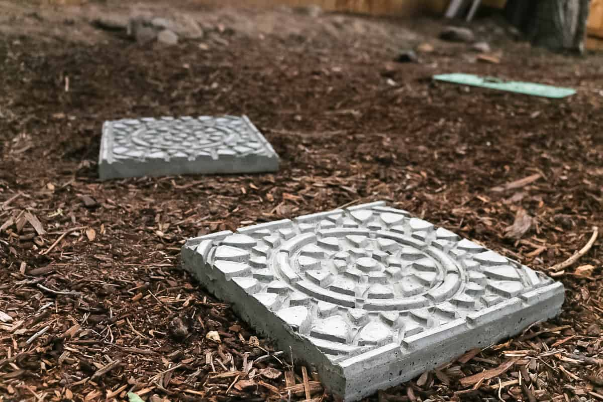 Two finished garden stepping stones on the ground.