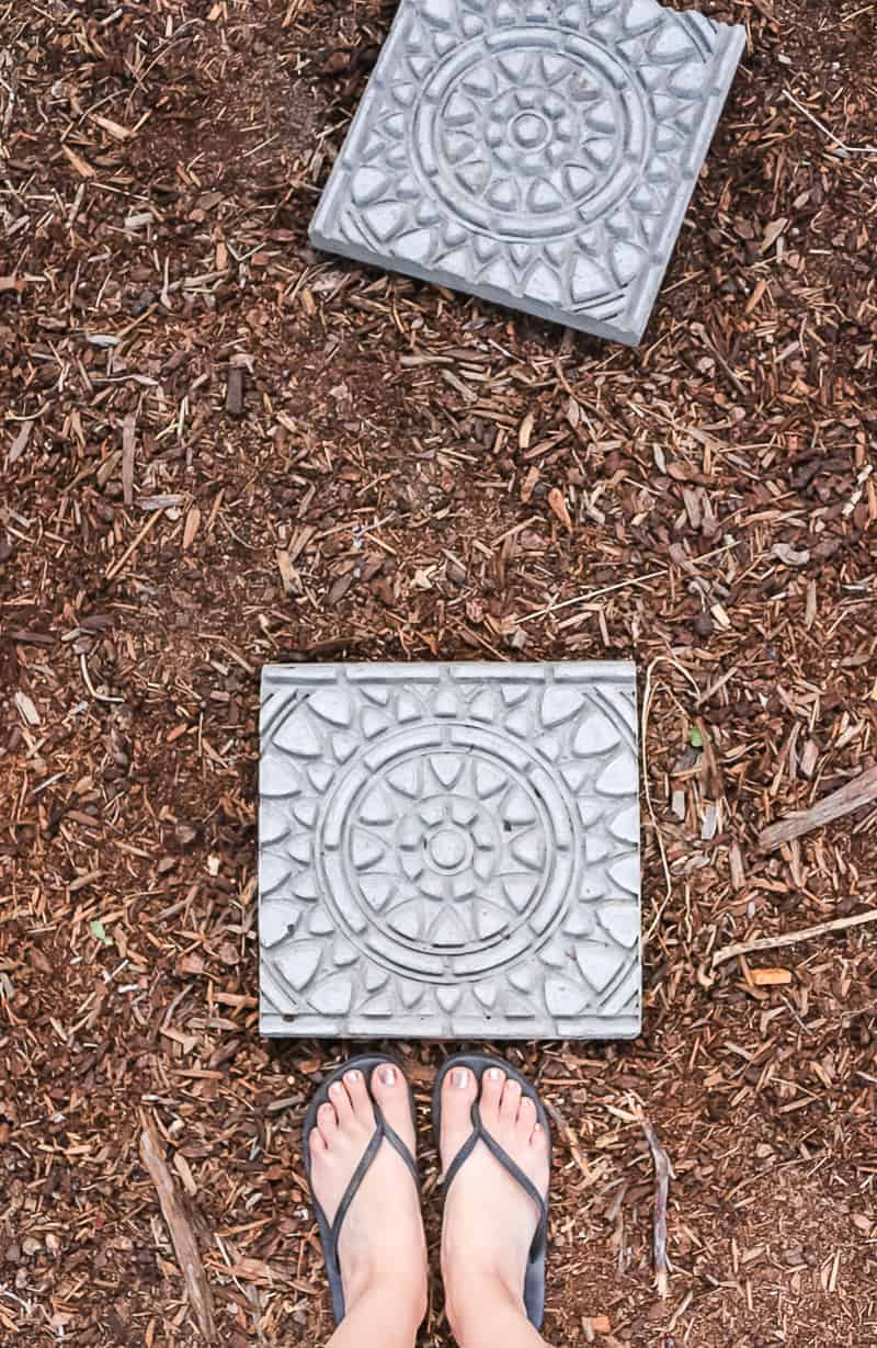 Photo of garden stepping stones with feet on the ground.