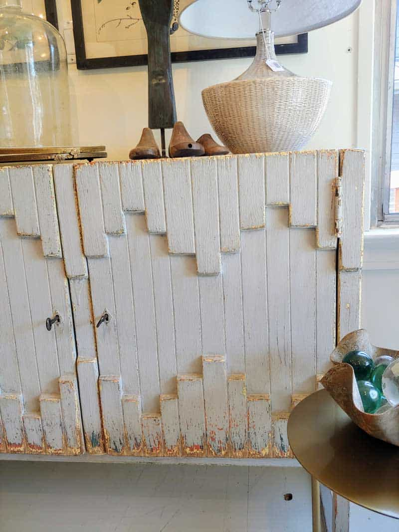 White vintage boho style cabinet with farmhouse home decor above it.