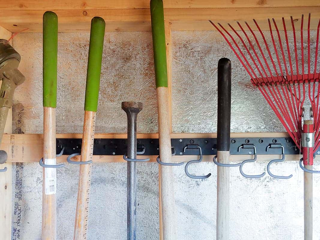 Garden tools hanged neatly in wall mounted hooks.
