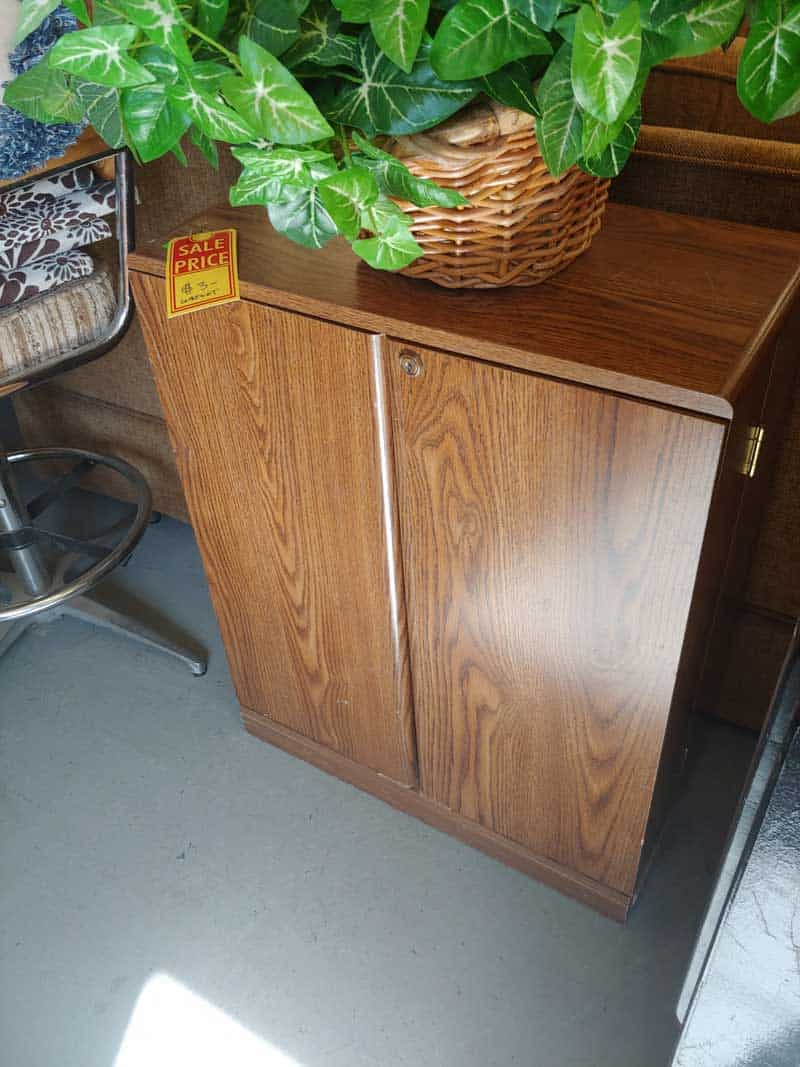 Old Media VHS storage cabinet in a thrift store with a sale tag of  on it with a basket of artificial plant above before photo