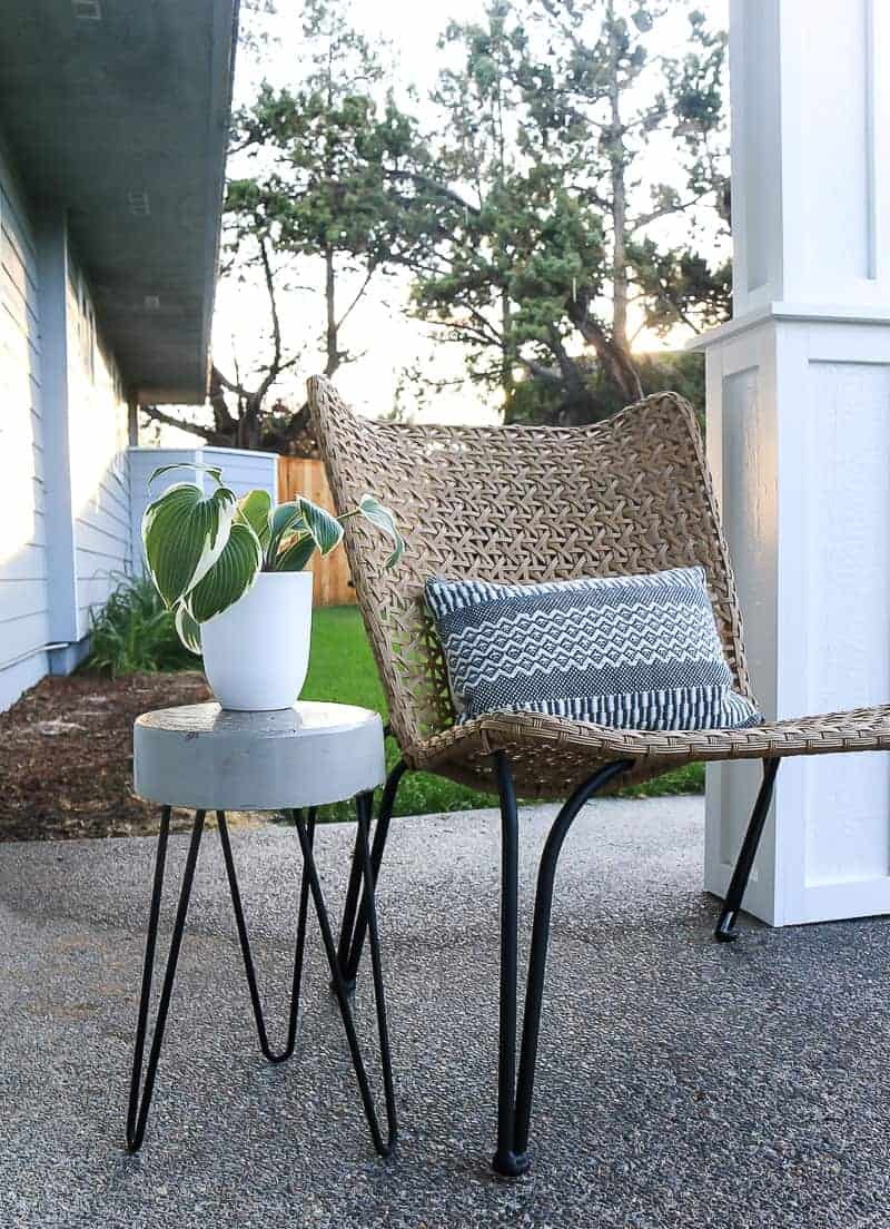 White planter on top of the concrete side table and farmhouse chair and pillow on the porch