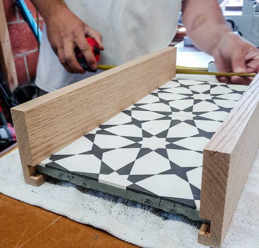Cement tiles with wood on each side and man measuring the other sides of the diy serving tray