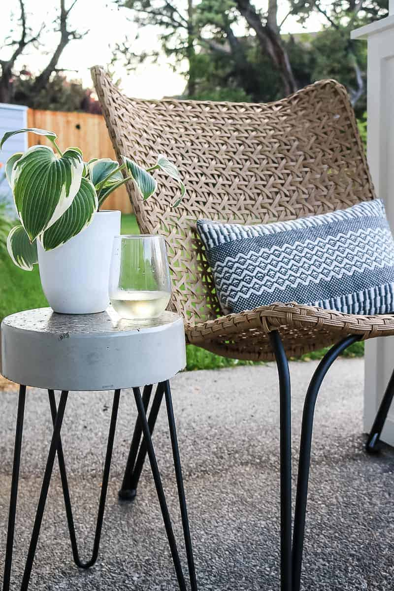 Closer shot of white planter, glass with water on top of the concrete side table beside the farmhouse chair and throw pillow