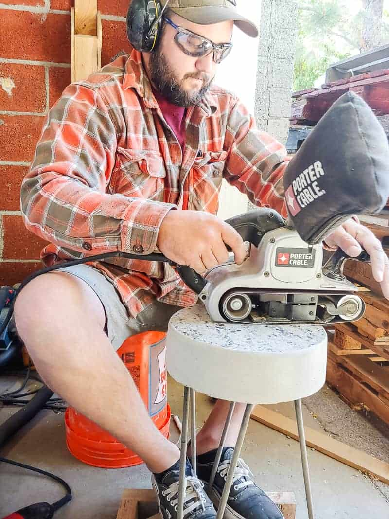 Man using a grinder to finish the top of the concrete side table.