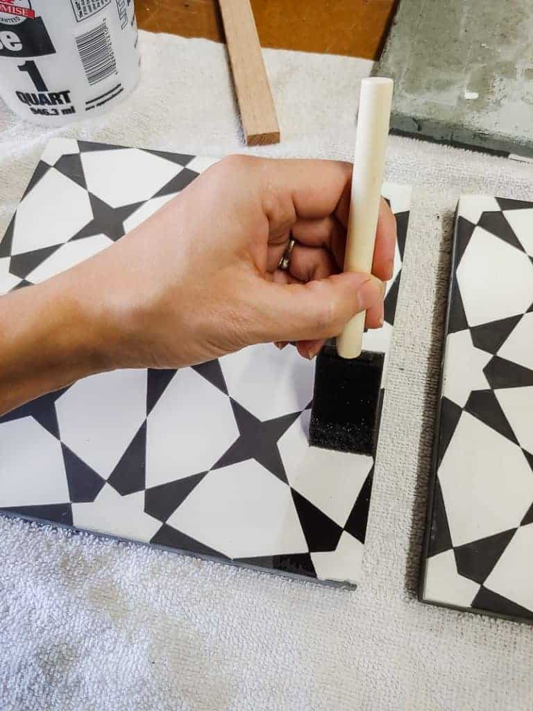 Applying seal to cement tile with foam paint brush