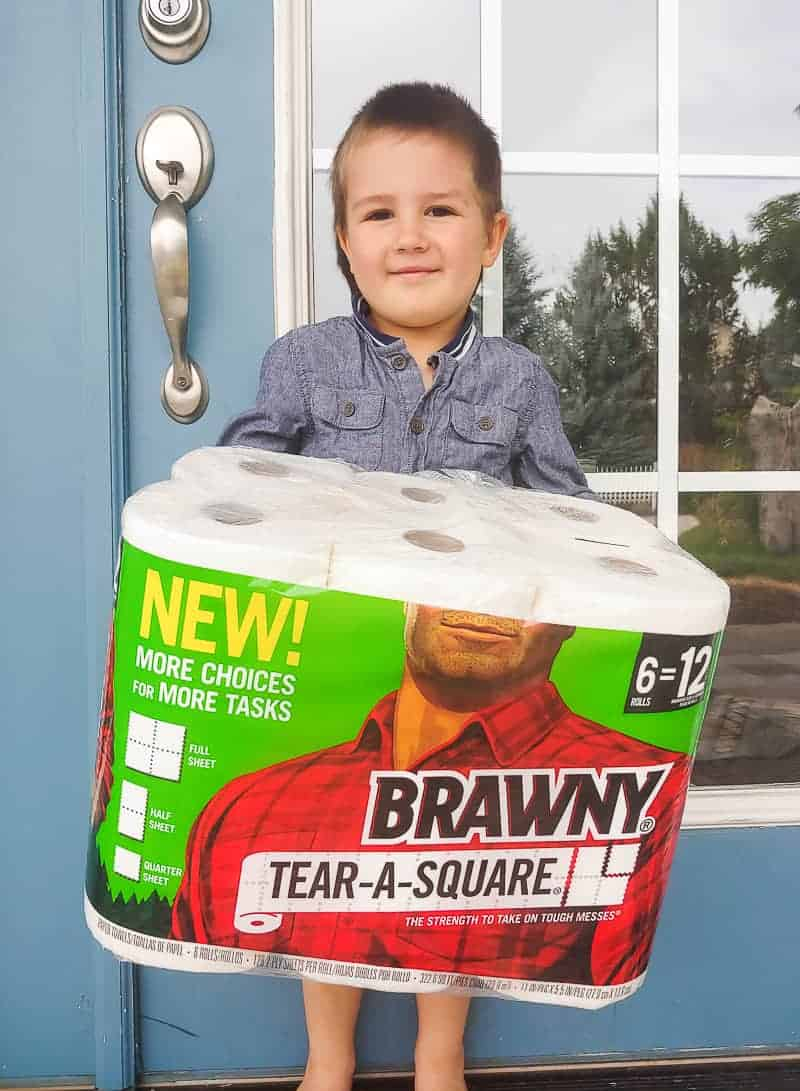 Preschooler boy holding a pack of paper towels