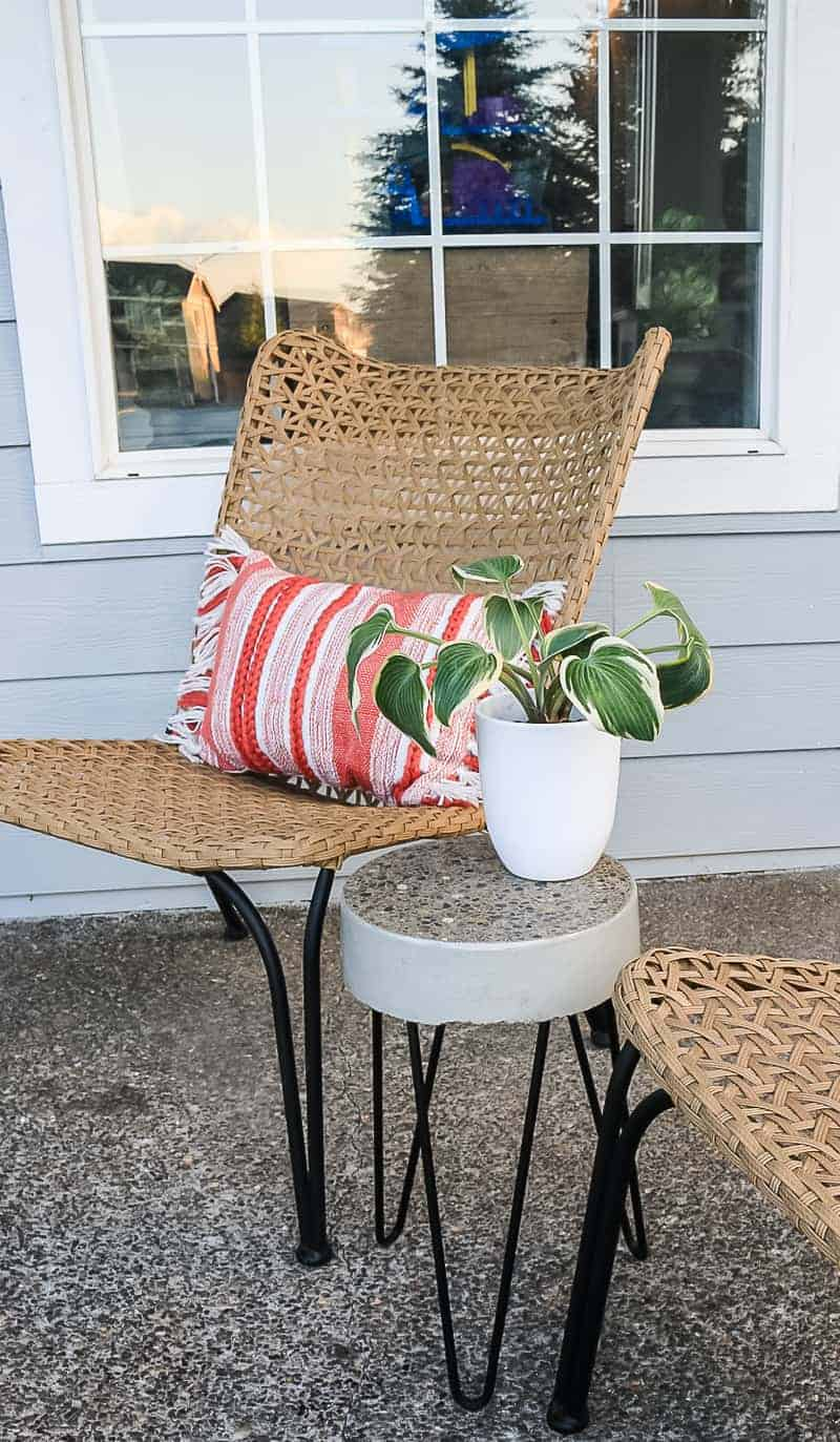 Standing concrete side table on the porch beside the farmhouse chairs and pillow.
