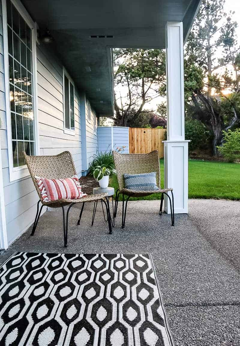 Porch chairs and a concrete side table in the center with lawn and fence in background and modern black and white outdoor rug as doormat