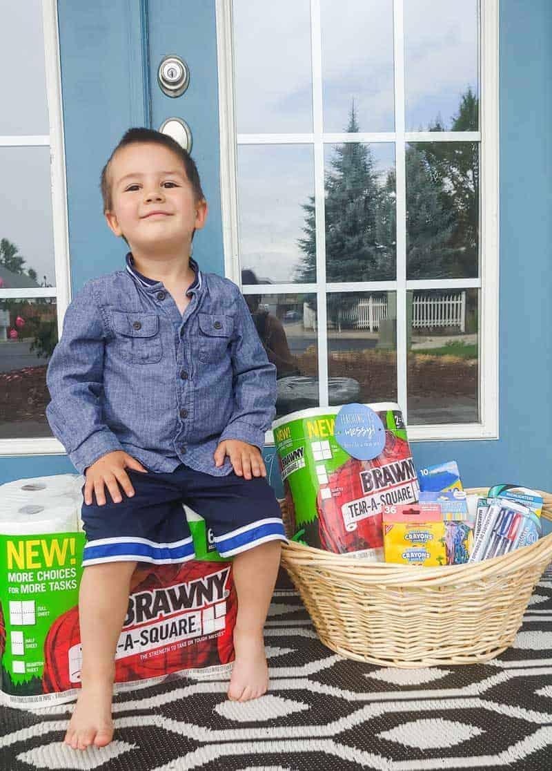 Preschooler boy sitting on the paper towel pack and a teacher gift set basket beside him