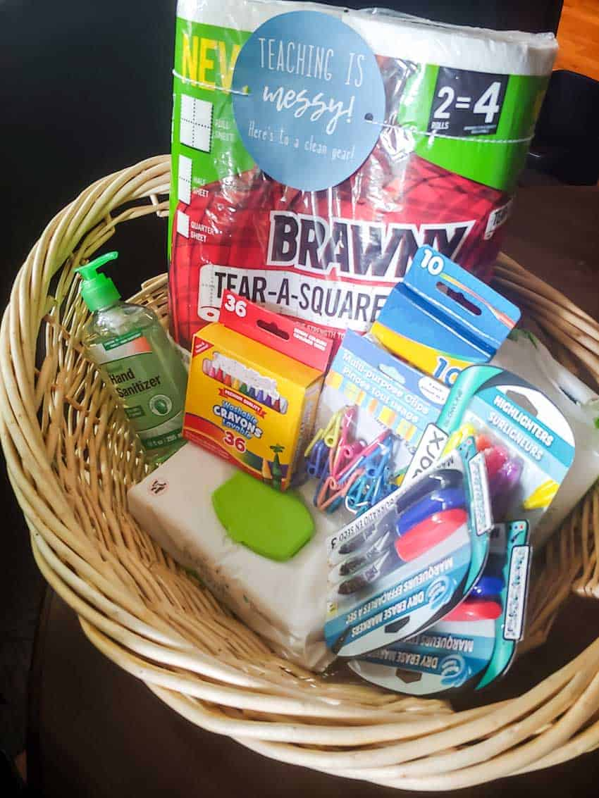 Basket filled with paper towel pack, hand sanitizer, crayons, clips and pens for the teacher gift set.