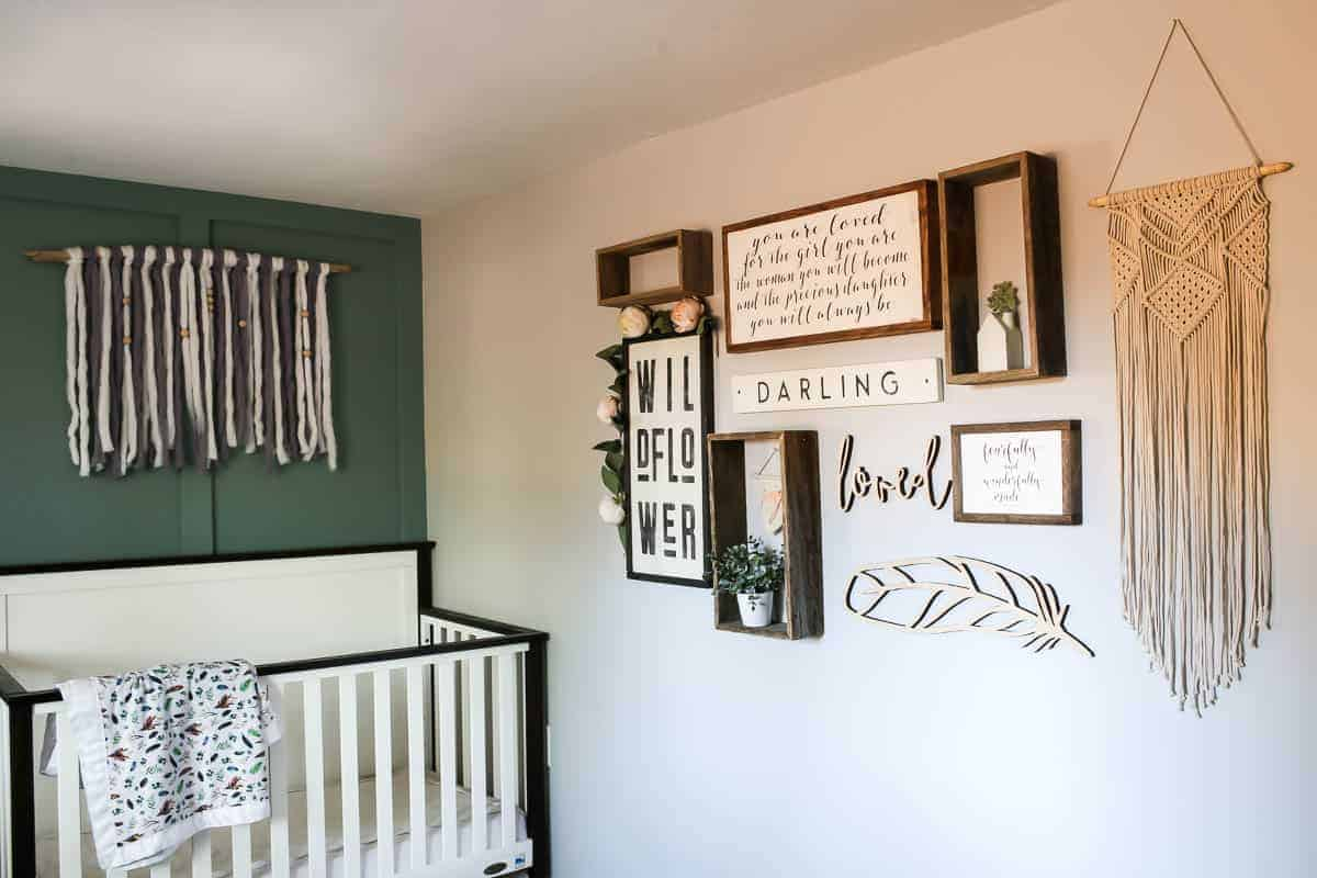 Nursery decor perfect for a baby girl's nursery with green accent wall, yarn wall art and gallery wall with white crib